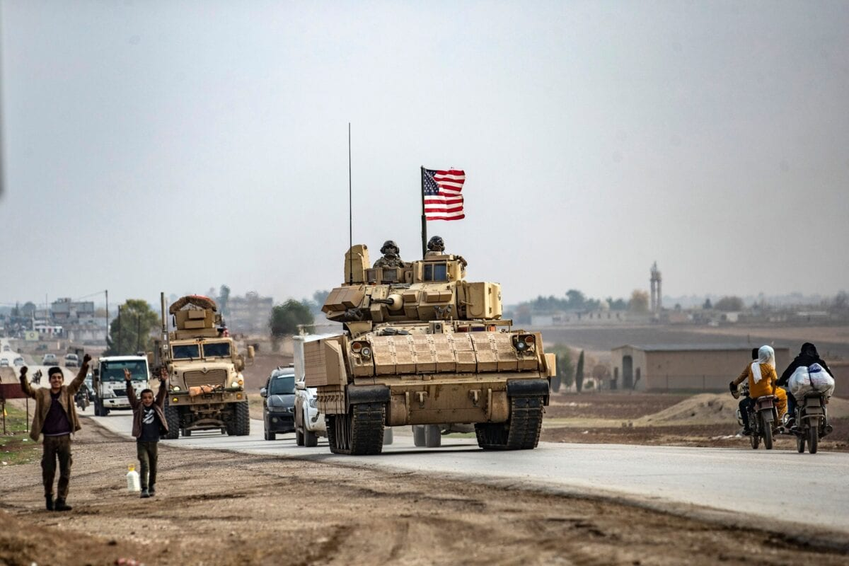 US troops patrol in their military vehicles near the border with Turkey, on December 17, 2020 [DELIL SOULEIMAN/AFP via Getty Images]