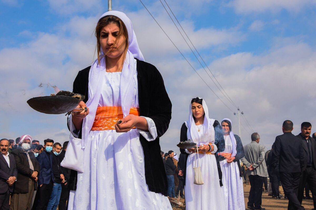 Women burn incense in a procession during a mass funeral for Yazidi victims of the Islamic State (IS) group in the northern Iraqi village of Kojo in Sinjar district, on February 6, 2021 [ZAID AL-OBEIDI/AFP via Getty Images]