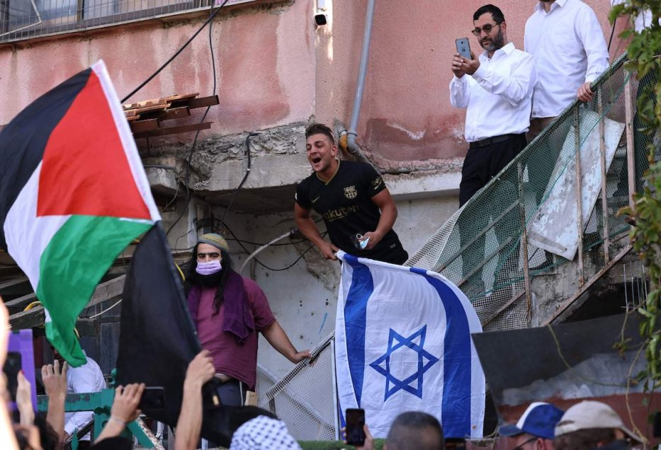 Israeli settlers in the Palestinian neighbourhood of Sheikh Jarrah react as Palestinian and Israeli activists chant slogans in front of their house during a demonstration against the expulsion of Palestinian families from their homes in Israeli-annexed east Jerusalem on 16 April 2021. [EMMANUEL DUNAND/AFP via Getty Images]
