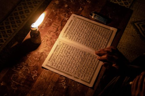 A student reads the Quran by candlelight on May 2, 2021 [Ulet Ifansasti/Getty Images]