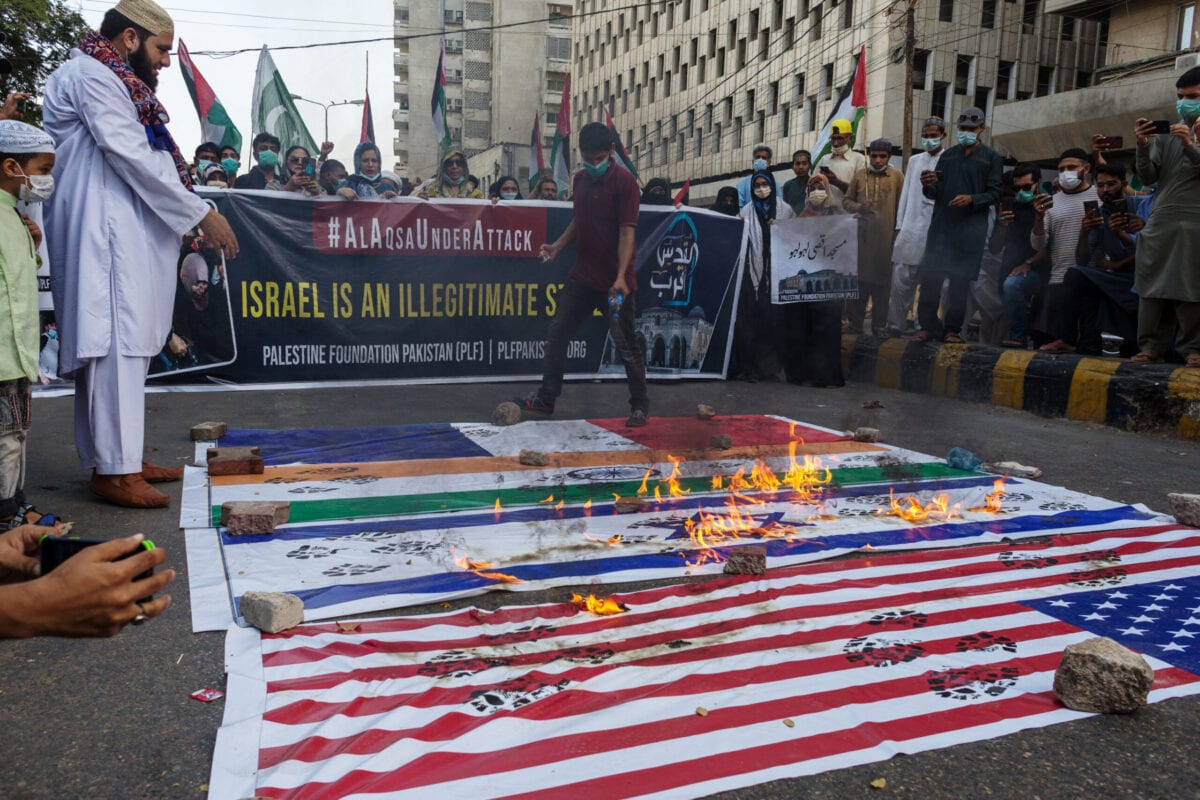 Demonstrators burn the flags of the US, Israel, India and France as they protest against Israel's military action in Gaza, in Karachi, Pakistan, on Tuesday, May 11, 2021 [Asim Hafeez/Bloomberg via Getty Image]