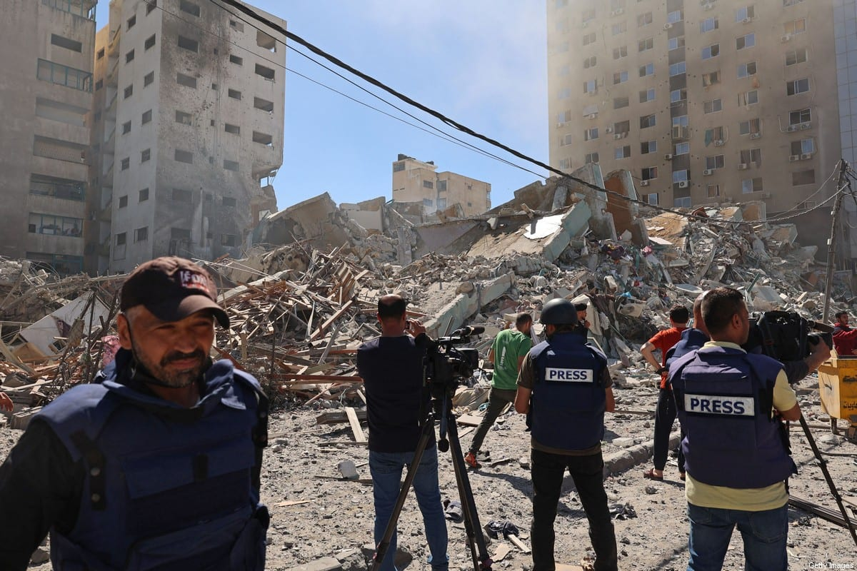 Palestinian journalists cover the destroyed Jala Tower, which was housing international press offices, following an Israeli airstrike in the Gaza Strip on May 15, 2021. [MOHAMMED ABED/AFP via Getty Images]