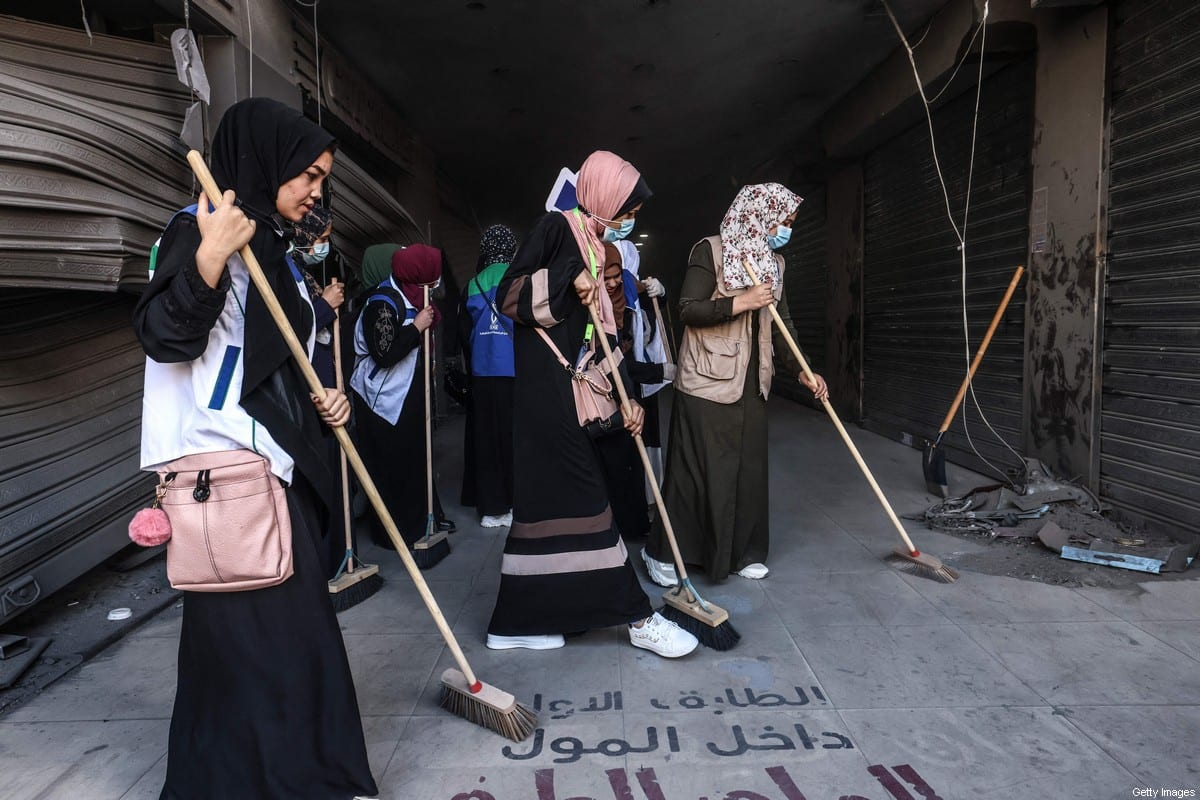 Volounteers clean up an alley in the Al-Remal commercial district in Gaza City, recently targeted by Israeli air strikes, on May 23, 2021[EMMANUEL DUNAND/AFP via Getty Images]