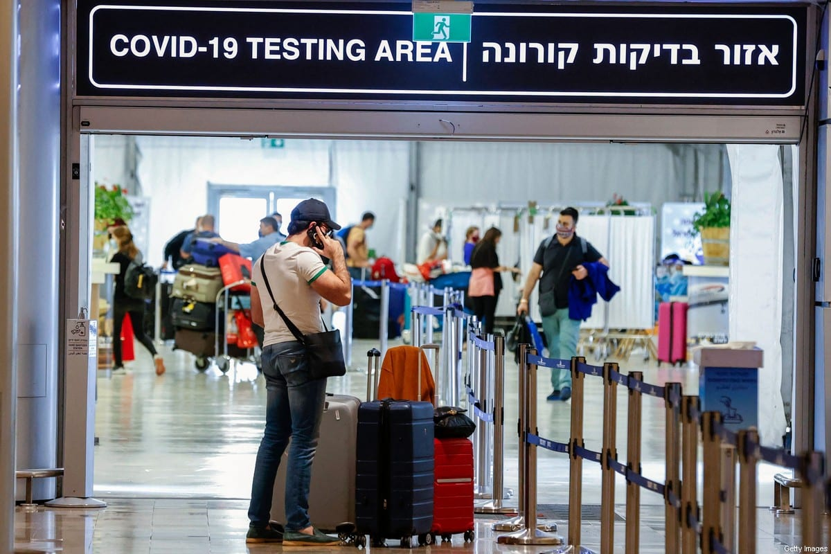Vaccinated tourists wearing masks for COVID-19 protection arrive to Israel's Ben Gurion Airport near Tel Aviv on May 23, 2021 [JACK GUEZ/AFP via Getty Images]