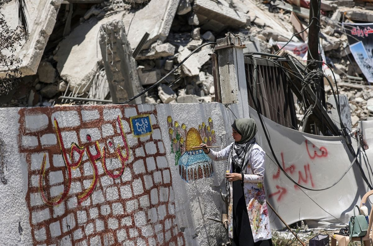 Palestinian artist Etaf al-Najili paints Al-Aqsa Mosque's Dome of the Rock in Jerusalem, on a remaining wall section of a damaged building in Gaza City, on 24 May 2021. [MAHMUD HAMS/AFP via Getty Images]