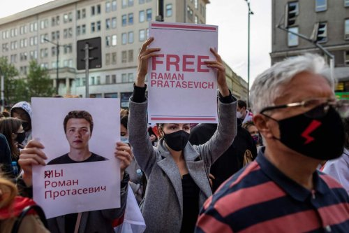 Belarusians living in Poland and Poles supporting them hold up a placard reading 'Free Roman Protasevich' during a demonstration in front of the European Commission office in Warsaw on 24 May 2021, demanding freedom for Belarus opposition activist Roman Protasevich a day after a Ryanair flight from Athens to Vilnius carrying the dissident journalist was diverted while in Belarusian airspace. [WOJTEK RADWANSKI/AFP via Getty Images]