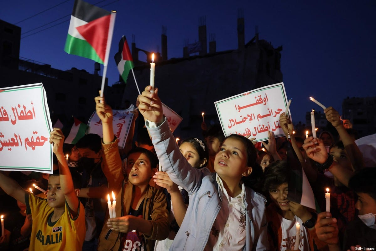 Palestinian children hold candles during a rally amid the ruins of houses destroyed by Israeli strikes, in Gaza City on 24 May 2021 [MOHAMMED ABED/AFP/Getty Images]