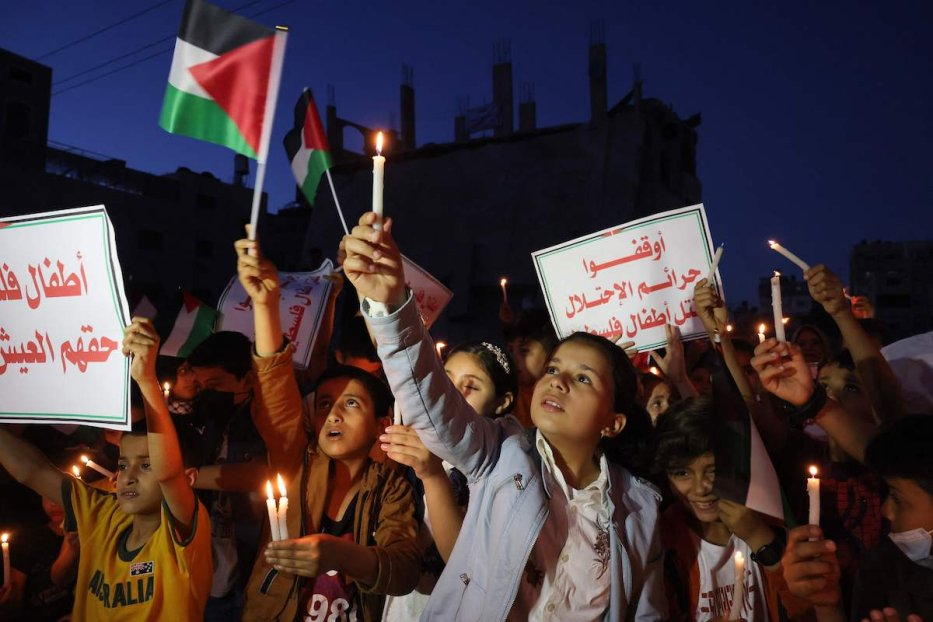"""Palestinian children hold candles during a rally amid the ruins of houses destroyed by Israeli strikes, in Gaza City on May 24, 2021. Slogans in Arabic reads: """"Stop the crimes of the occupation of Palestine. - A ceasefire was reached late last week after 11 days of deadly violence between Israel and the Hamas movement which runs Gaza, stopping Israel's devastating bombardment on the overcrowded Palestinian coastal enclave which, according to the Gaza health ministry, killed 248 Palestinians, including 66 children, and wounded more than 1,900 people. Meanwhile, rockets from Gaza claimed 12 lives in Israel, including one child and an Israeli soldier. (Photo by MOHAMMED ABED / AFP) (Photo by MOHAMMED ABED/AFP via Getty Images)"""