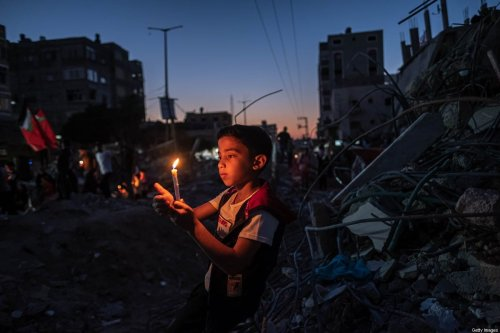 A Palestinian child holds candle amid the ruins of house destroyed by Israeli air strikes, in Gaza Strip on 25 May 2021 [Fatima Shbair/Getty Images]