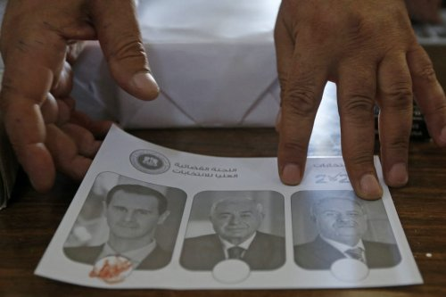 A Syrian votes for President Bashar al-Assad by marking the ballot with blood at a polling station in Damascus on 26 May 2021 [LOUAI BESHARA/AFP via Getty Images]
