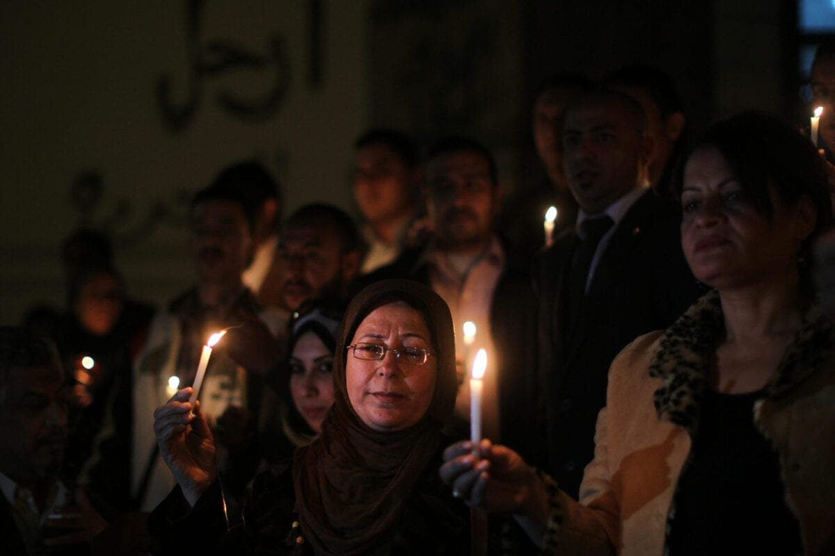 Egyptians hold candles at the entrance of the jounalist's sydicate in Cairo on December 31, 2012 [MAHMUD HAMS/AFP via Getty Images]