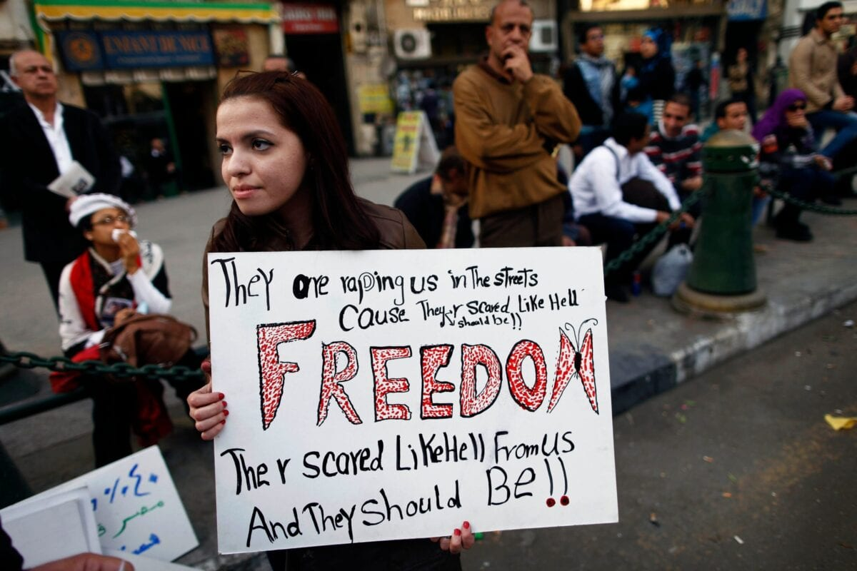 An Egyptian woman holds a banner as she marches in downtown Cairo to mark International Women's Day on March 8, 2013 [MAHMUD KHALED/AFP via Getty Images]