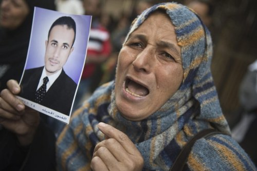 An Egyptian woman holding the portrait of a relative on April 28, 2014 in the southern city of Minya [KHALED DESOUKI/AFP via Getty Images]