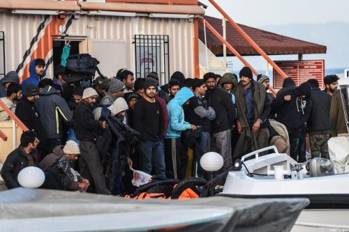 """Captured Afghani migrants disembark from a Turkish coast guard boat in the morning on April 4, 2016 in the port of Dikili district in Izmir, after trying to cross to Greek island Lesbos. Greece sent a first wave of migrants back to Turkey on April 4 under an EU deal that has faced heavy criticism from rights groups. Under the agreement, designed to halt the main influx which comes from Turkey, all """"irregular migrants"""" arriving since March 20 face being sent back, although the deal calls for each case to be examined individually. For every Syrian refugee returned, another Syrian refugee will be resettled from Turkey to the EU, with numbers capped at 72,000. / AFP / OZAN KOSE (Photo credit should read OZAN KOSE/AFP via Getty Images)"""