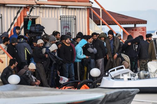 Afghani migrants disembark from a Turkish coast guard boat in the morning on April 4, 2016 in the port of Dikili district in Izmir [OZAN KOSE/AFP via Getty Images]