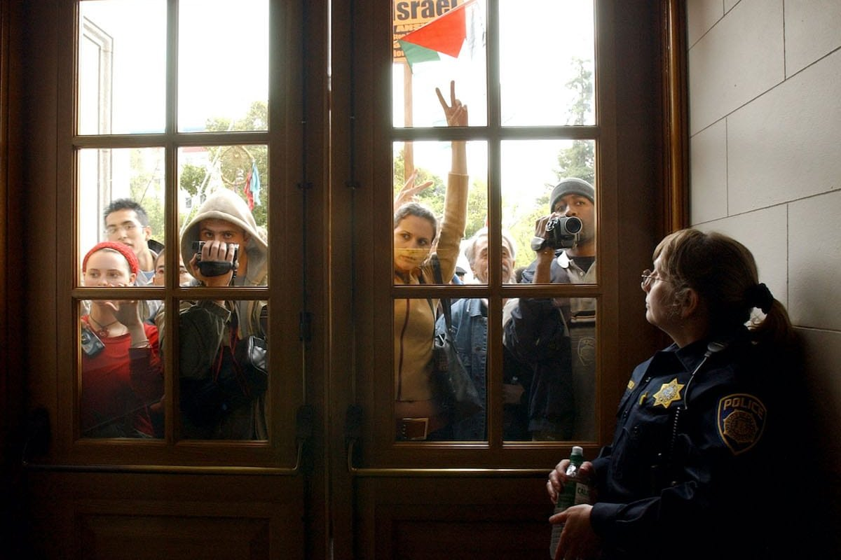 University of California at Berkeley police officer Debra Schnek guards a door to a building where dozens of pro-Palestinian demonstrators held a sit-in during a protest April 9, 2002 at the school in Berkeley, CA. [Justin Sullivan/Getty Images]