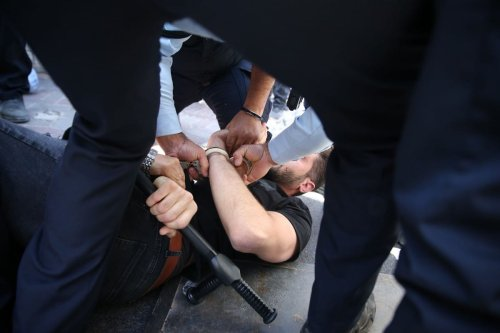 Israeli police take a Palestinian into custody during a protest against the Israeli court to evacuate the homes of Palestinian families in Jerusalem on 26 May 2021 [Mostafa Alkharouf/Anadolu Agency]