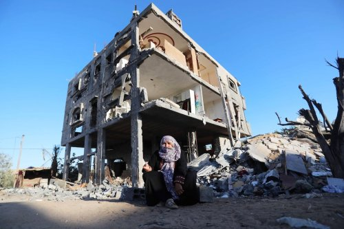 A Palestinian woman sits in front of a house damaged by Israeli attacks in Gaza on 7 June 2021 [Ashraf Amra/Anadolu Agency]