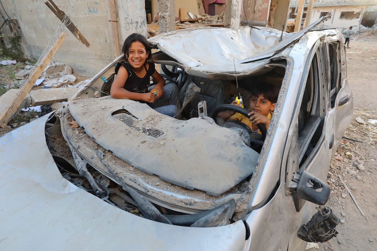 Palestinian children are seen playing in a car wrecked by the Israeli attacks in Beit Lahia, Gaza on June 07, 2021 [Ashraf Amra / Anadolu Agency]