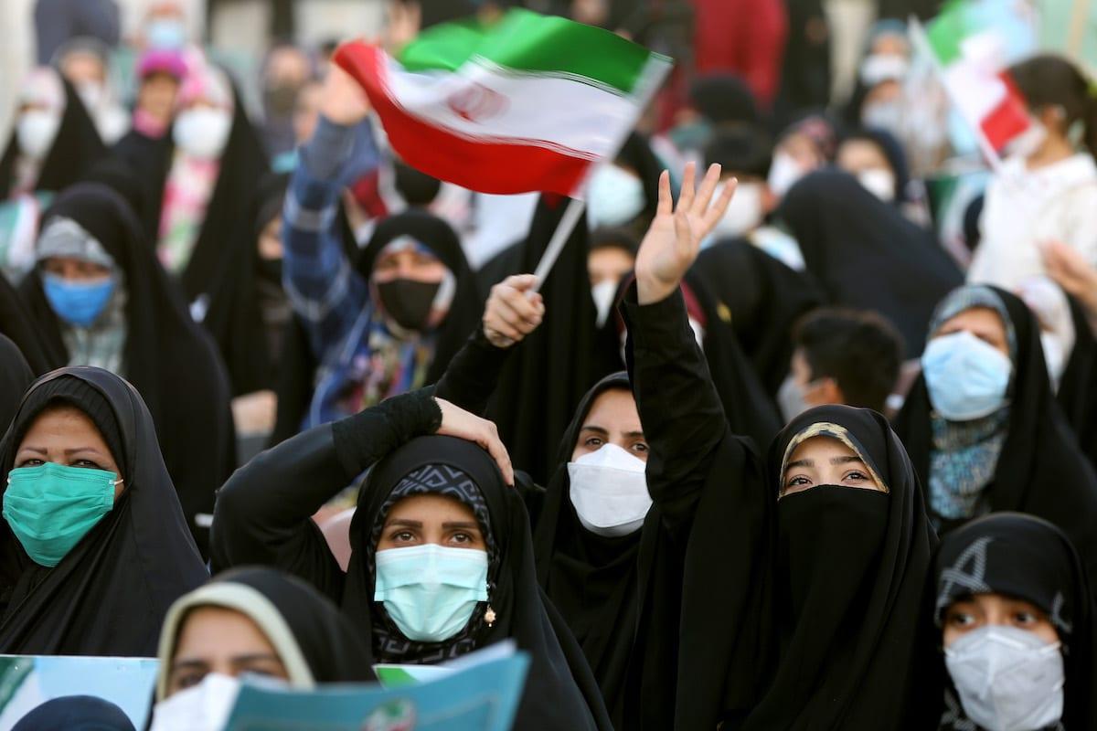 Apoiadores do então candidato presidencial Ebrahim Raisi, segurando bandeiras iranianas e as fotos dele se reúnem durante um comício antes das eleições presidenciais iranianas a serem realizadas em 18 de junho, na Praça Hafte Tir em Teerã, Irã, em 14 de junho de 2021 [Fatemeh Bahrami / Agência Anadolu]