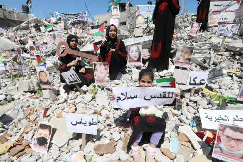 Photos of children, who lost their lives in Israel's attacks on Gaza, are exhibited at debris of Es-Sekka family's house in Khan Yunis, Gaza on June 19, 2021 [Ashraf Amra/Anadolu Agency]