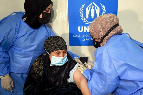 A patient receives the coronavirus vaccine in Amman, Jordan on 15 February 2021 [KHALIL MAZRAAWI/AFP/Getty Images]