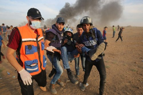 Palestinian paramedics and journalists carry a wounded fellow journalist during clashes with Israeli forces east of Gaza city on October 5, 2018 [SAID KHATIB/AFP via Getty Images]