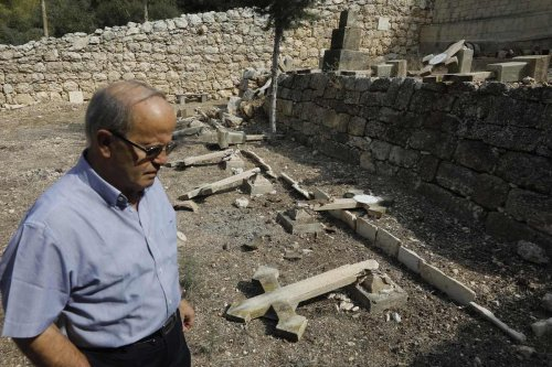 Father Antonio Scudu, caretaker of Saint Stephen Church in the Beit Jamal Salesian monastery, looks at overturned crosses in a graveyard that has reportedly been vandalised near the central Israeli town of Beit Shemesh, west of Jerusalem on 18 October 2018. [MENAHEM KAHANA/AFP via Getty Images]