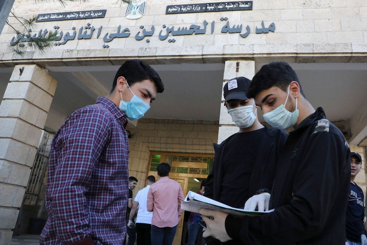 Palestinian students revise before entering their school for their final exams in the West Bank city of Hebron on 30 May 2020. [HAZEM BADER/AFP via Getty Images]