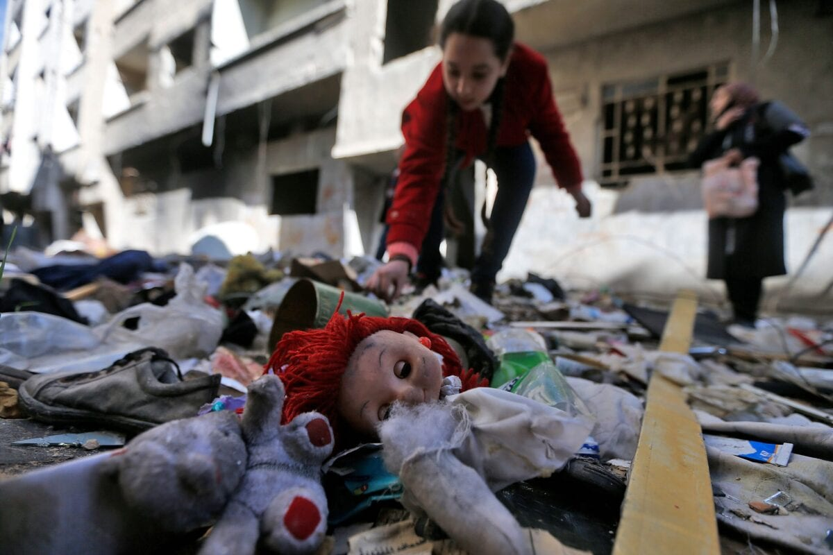 A girl looks through abandoned belongings in the rubble on the streets of the Palestinian Yarmuk camp, on the southern outskirts of the Syrian capital Damascus, on November 25, 2020 [LOUAI BESHARA/AFP via Getty Images]