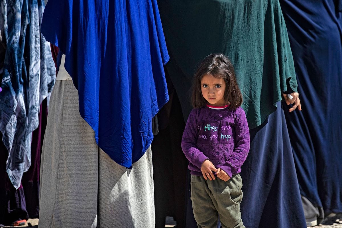A child poses at Camp Roj, where relatives of people suspected of belonging to Deash group are held, in the countryside near al-Malikiyah (Derik) in Syria's northeastern Hasakah province, on March 28, 2021. [DELIL SOULEIMAN/AFP via Getty Images]