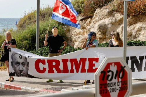 Israelis deploy a large banner as they take part in a sit in against Prime Minister Benjamin Netanyahu in front of the Carlton Hotel during a meeting of members of the Likud party and the prime minister, in the coastal city of Tel Aviv, on May 6, 2021 [JACK GUEZ/AFP via Getty Images]