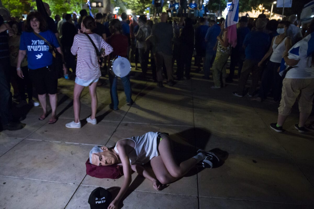 An Israeli woman with a mask of Israeli Prime Minister Benjamin Netanyahu lies down on the ground during a protest in support of a unity government to oust Netanyahu from office on May 31, 2021 in Tel Aviv, Israel [Amir Levy/Getty Images]