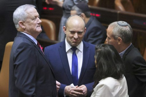 Israeli Defence Minister and leader of Blue and White party, Benny Gantz (L), speaks to Yamina leader, Naftali Bennett (C), during a special session of the Knesset to elect a new president, Israel's parliament, in Jerusalem on June 2, 2021 [RONEN ZVULUN/POOL/AFP via Getty Images]