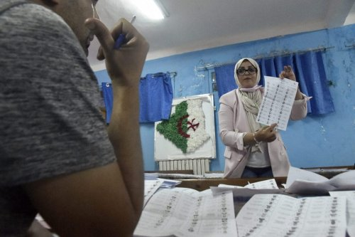 Algerian elections staff count ballots for parliamentary elections at a polling station in Bouchaoui, on the western outskirts of the capital Algiers, on June 12, 2021 [RYAD KRAMDI/AFP via Getty Images]