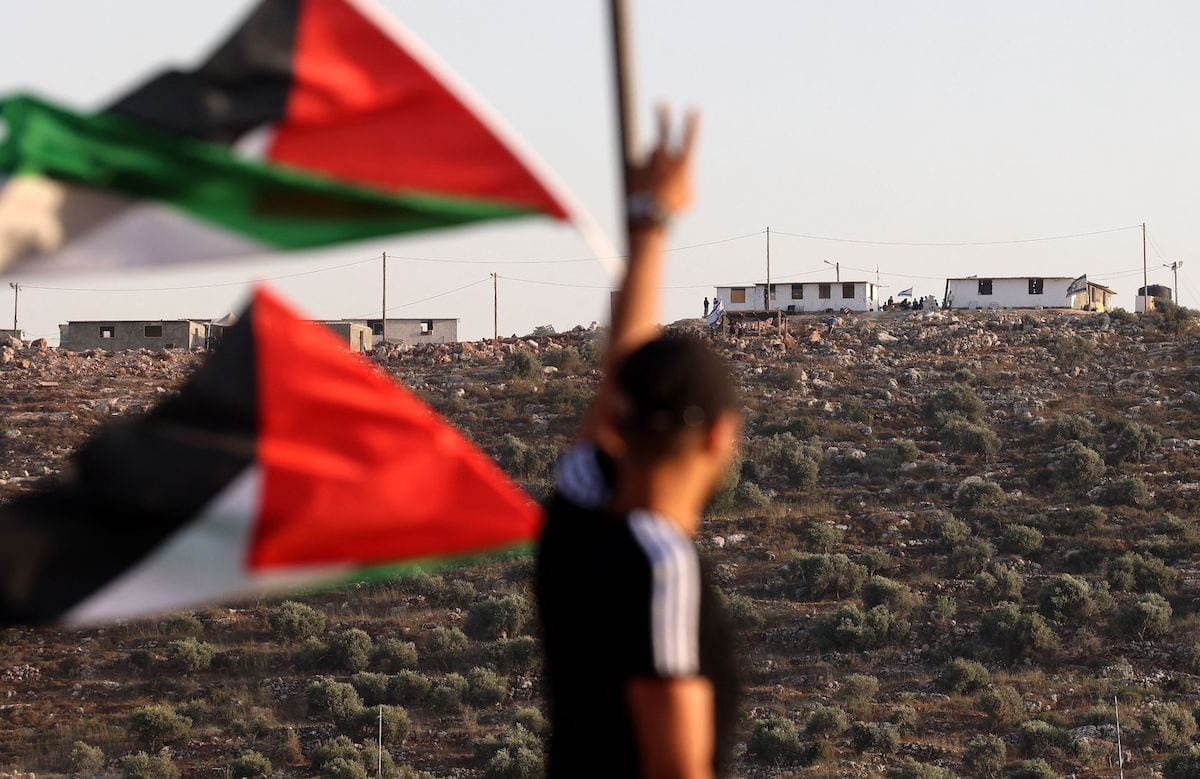 Palestinian flags flutter as a youth flashes the victory sign towards a new Israeli settler outpost in the village of Beita, south of Nablus in the occupied West Bank, on 13 June 2021. [JAAFAR ASHTIYEH/AFP via Getty Images]