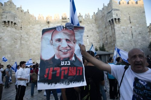"""A far right Israeli holds a poster with a photo of new Israeli Prime Minister Naftali Bennett saying in hebrew """"Liar"""" on June 15, 2021 in Jerusalem [Amir Levy/Getty Images]"""