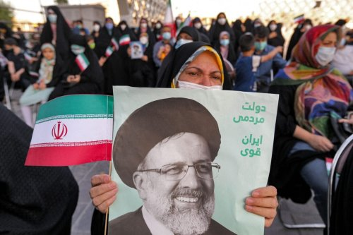 A woman holds a poster of Iran's newly-elected president Ebrahim Raisi [ATTA KENARE/AFP via Getty Images]