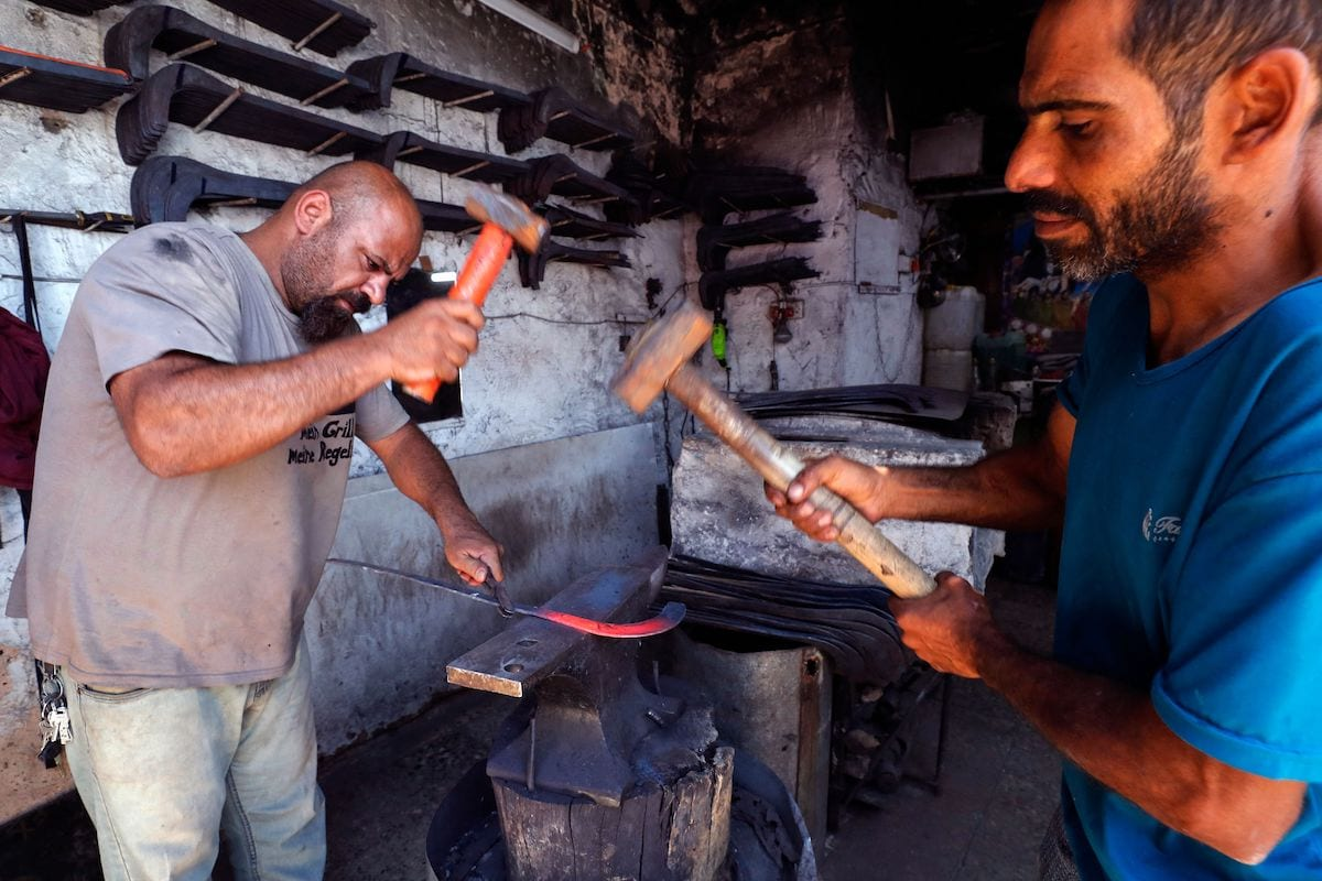 Iraqi blacksmiths manufacture an agricultural sickle at a workshop in the Al-Alawi district of the capital Baghdad, on 20 June 2021. [AHMAD AL-RUBAYE/AFP via Getty Images]