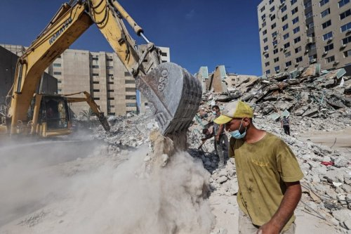 Palestinian workers collect the rubble of Al-Jalaa tower in Gaza City on June 22, 2021 [MOHAMMED ABED/AFP via Getty Images]