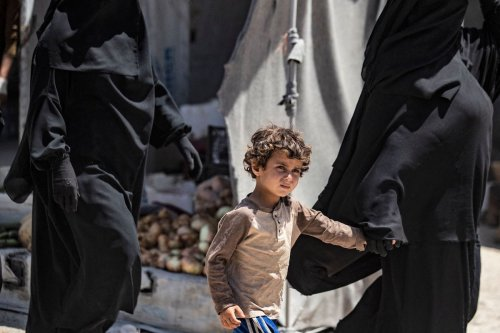 A woman walks with a child at the Kurdish-run al-Hol camp, which holds relatives of suspected Islamic State (IS) group fighters, in Hasakeh governorate in northeastern Syria, on June 23, 2021. [DELIL SOULEIMAN/AFP via Getty Images]