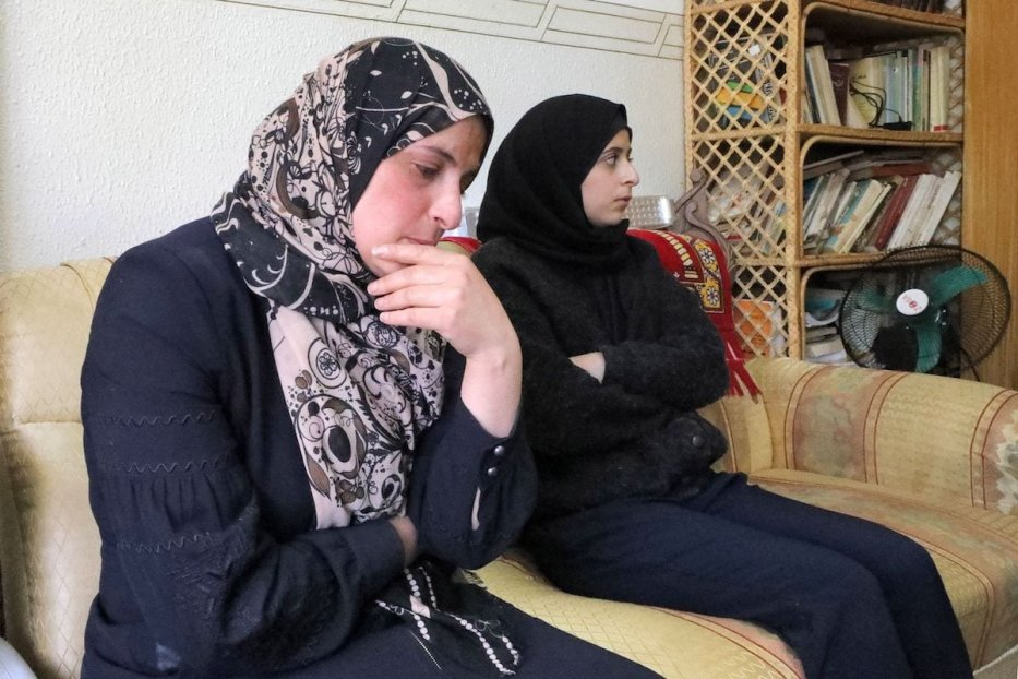 The wife (L) of the Palestinian activist Nizar Banat, who died during his arrest by Palestinian security forces, grieves in her house in the village of Dura near Hebron in the occupied West Bank, on 24 June 2021. [MOSAB SHAWER/AFP via Getty Images]