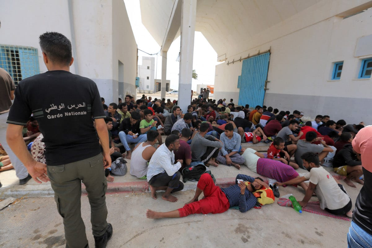 Migrants of South Asian origin rescued by Tunisia's national guard during an attempted crossing of the Mediterranean by boat rest at the port of el-Ketef in Ben Guerdane in southern Tunisia near the border with Libya on 24 June 2021. [FATHI NASRI/AFP via Getty Images]