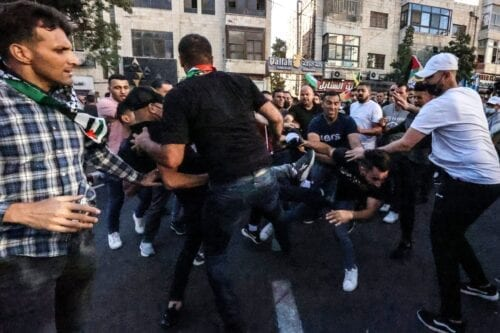 Palestinian supporters of President Mahmoud Abbas scuffle with protesters demanding his resignation, as they demonstrate in the occupied West Bank city of Ramallah on June 27, 2021, days after the death of human rights activist Nizar Banat while in the custody of Palestinian Authority (PA) security forces [ABBAS MOMANI/AFP via Getty Images]