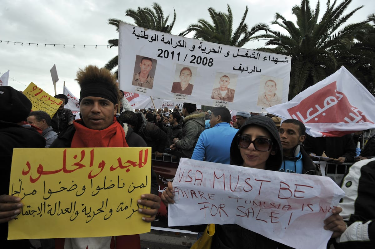 A delegation of people from Redeyef, in the Gafsa Mining Basin, hold pictures and placards during a protest against the decision taken by the National Constituent Assembly (NCA) on 17 January 2013 outside the NCA building in Tunis. [FETHI BELAID/AFP via Getty Images]