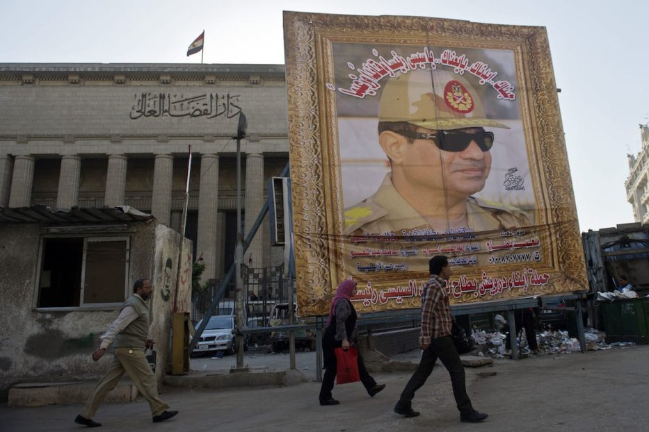 Egyptian walk past a huge poster of Egypt's former Defence Minister and armed forces chief General Abdul Fatah Al-Sisi outside the High Court in downtown Cairo, on 27 March 2014. [KHALED DESOUKI/AFP via Getty Images]