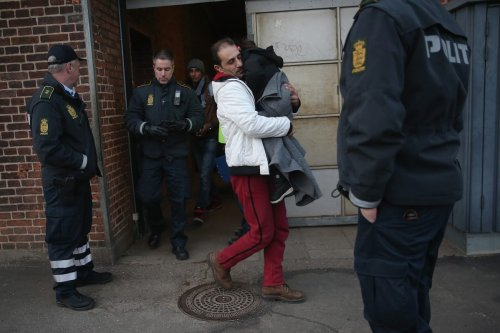 Danish police escort a family from Syria seeking asylum in Denmark after finding them while checking the identity papers of passengers on a train arriving from Germany on January 6, 2016 in Padborg, Denmark. [Sean Gallup/Getty Images]