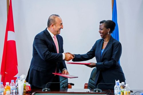Turkish Minister for Foreign Affairs Mevlut Cavusoglu (L) and Rwandan Minister for Foreign Affairs Louise Mushikiwabo (R) shake hands as they exchange folders after the signing of different Memorandum of understanding (MOU) in Kigali on 31 May 2016. [CYRIL NDEGEYA/AFP via Getty Images]