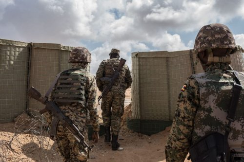 Soldiers serving in the African Union Mission in Somalia (AMISOM) exit AMISOM's Forward Operating Base before a patrol on October 11, 2016 in Barawe, Somalia [Andrew Renneisen/Getty Images]
