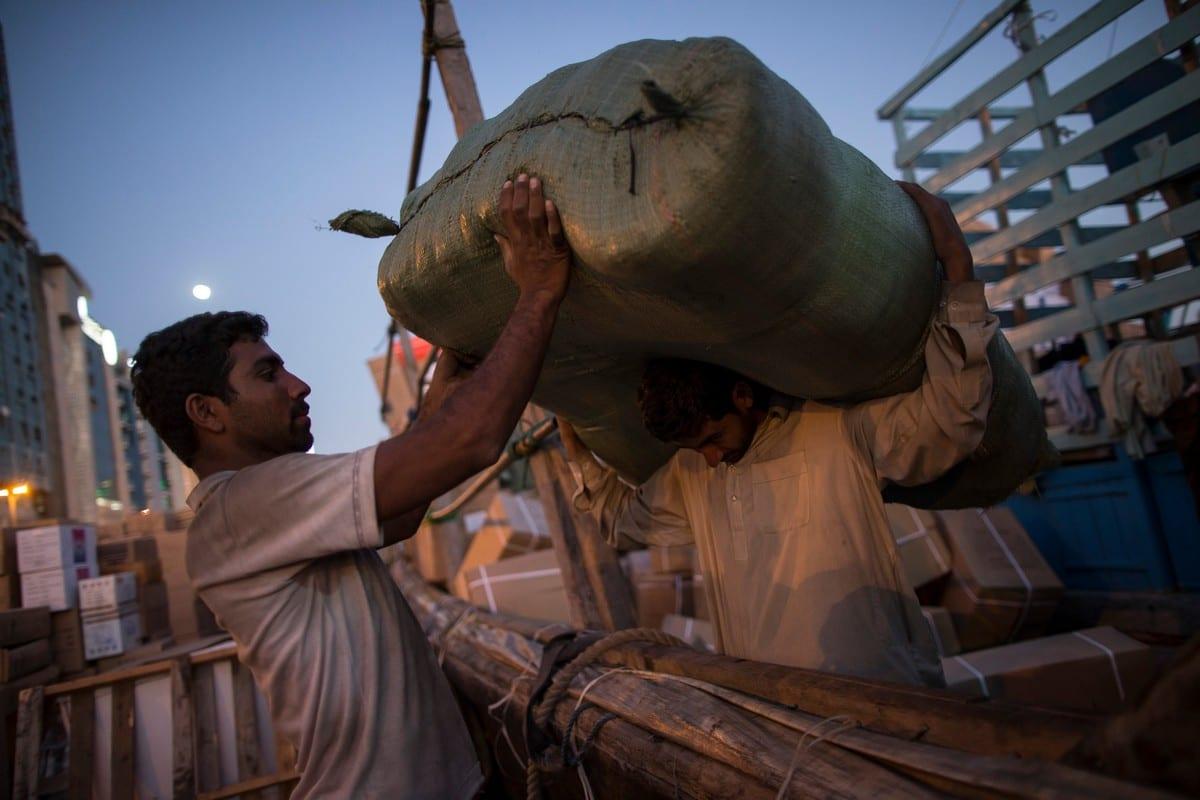 Pakistani labourers load a ship in Dubai, UAE on 2 February 2015 [Dan Kitwood/Getty Images]